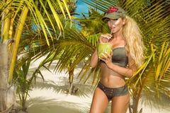 Beautiful, sexy girl in bikini, posing on the Caribbean beach and holding a coconut. Beautiful, sexy girl model in bikini, posing on the Caribbean beach and stock photo