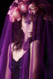 Beautiful sexy girl with black hair in a black lace dress with a wreath on his head covered with a violet veil in the Studio Royalty Free Stock Photography