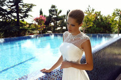 Beautiful sexy girl with blond hair in elegant wedding dress. Fashion outdoor photo of beautiful sexy girl with blond hair in elegant wedding dress posing Stock Photography