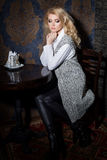 Beautiful sexy girl with blond hair sitting in a cafe with a cup of coffee in a warm sweater Royalty Free Stock Photo