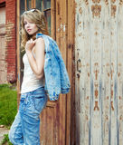 Beautiful sexy girl blonde near an old abandoned house in sunglasses with large plump lips in jeans and a jacket. Beautiful sexy girl blonde near an old Royalty Free Stock Photos