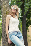 Beautiful girl blonde in the Park in sunglasses with large plump lips standing near a tree Royalty Free Stock Image