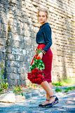 Beautiful and girl with a bouquet of red roses stands on the background of an old brick wall. stock image