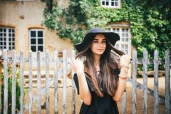 Beautiful sexy girl brunette with brown eyes in a black dress and a black hat with big brims against the backdrop of a wooden fenc. E and an old house in a Stock Photography