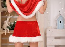 Beautiful sexy girl with curly hair in Santa Claus clothes back view Royalty Free Stock Image