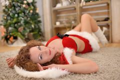 Beautiful sexy girl with curly hair in Santa Claus clothes posing on warm rug Royalty Free Stock Image