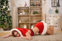Beautiful sexy girl with curly hair in Santa Claus clothes posing on warm rug Stock Photo