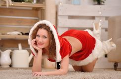 Beautiful sexy girl with curly hair in Santa Claus clothes posing on warm rug Royalty Free Stock Photography
