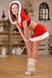 Beautiful sexy girl with curly hair in Santa Claus clothes smiling Royalty Free Stock Images