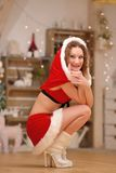 Beautiful sexy girl with curly hair in Santa Claus clothes squats Royalty Free Stock Image