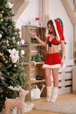 Beautiful sexy girl with curly hair in Santa Claus clothes Royalty Free Stock Image