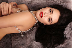 Beautiful girl with dark hair with luxurious bijou necklace. Fashion interior photo of beautiful girl with dark hair with luxurious bijou necklace,lying on fur royalty free stock photos