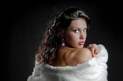 Beautiful girl in fur coat on black Stock Images