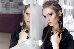 Beautiful sexy girl with hair in the style of rock stands near the mirror in the dressing room in a black velvet gown with a brigh Royalty Free Stock Photography