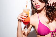 Beautiful sexy girl holding cocktail wearing bikini over white background Royalty Free Stock Photos
