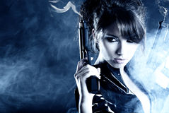 Beautiful sexy girl holding gun. Smoke background Stock Images