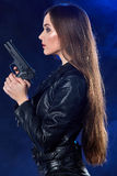 Beautiful sexy girl holding gun . smoke background Royalty Free Stock Image