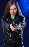 Beautiful girl holding gun . smoke background Royalty Free Stock Image