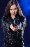 Beautiful girl holding gun . smoke background.  royalty free stock image