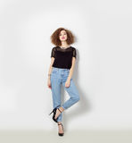 Beautiful sexy girl in jeans and a black t-shirt standing near a white wall, bright makeup and hairstyle, photo in Studio Stock Image