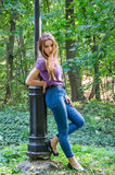 Beautiful sexy girl in jeans and jacket walking among the trees in autumn park and emotionally poses near a lantern Royalty Free Stock Photo