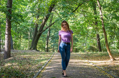 Beautiful girl in jeans and jacket walking among the trees in autumn park and emotionally poses near a lantern