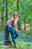 Beautiful sexy girl in jeans and jacket walking among the trees in autumn park and emotionally poses near a lantern Royalty Free Stock Photography