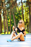 Beautiful sexy girl in jeans short sits on skateboard Royalty Free Stock Image