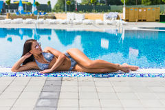 Beautiful sexy girl lies on the edge of the swimming pool sunbathing. Summer vocation. Beautiful sexy girl lies on the edge of the swimming pool sunbathing Royalty Free Stock Photo