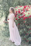 Beautiful sexy girl in a light dress with delicate make-up and hair in a flower garden with roses in luchas sunlight at sunset. St. Beautiful sexy girl in a Stock Images