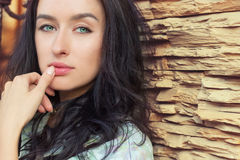 Beautiful girl with long black hair with green eyes standing near a brick wall Royalty Free Stock Image