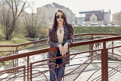Beautiful girl with long dark hair in sunglasses walking around the sunny city Royalty Free Stock Photo