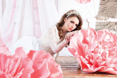 Beautiful sexy girl in a long dress with a huge pink flowers sit Royalty Free Stock Photography