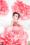 Beautiful sexy girl in a long dress with a huge pink flowers sitting by the window Royalty Free Stock Photography