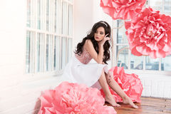 Beautiful sexy girl in a long dress with a huge pink flowers sitting by the window Stock Photography