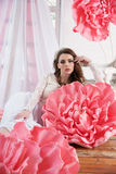 Beautiful sexy girl in a long dress with a huge pink flowers sitting by the window Royalty Free Stock Photo