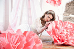 Beautiful sexy girl in a long dress with a huge pink flowers sitting by the window Stock Photos