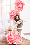 Beautiful sexy girl in a long dress with a huge pink flowers sitting by the window Royalty Free Stock Image