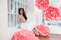 Beautiful sexy girl in a long dress with a huge pink flowers sitting by the window Royalty Free Stock Photos