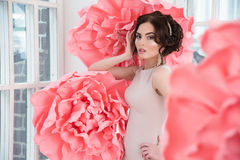 Beautiful sexy girl in a long dress with a huge pink flowers sitting by the window Stock Photo