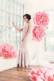 Beautiful sexy girl in a long dress with a huge pink flowers. Royalty Free Stock Photo