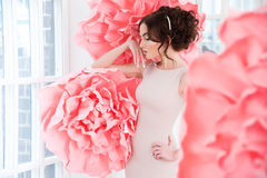 Beautiful sexy girl in a long dress with a huge pink flowers. Royalty Free Stock Photos