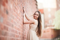 Beautiful sexy girl with long hair and dress perfect shape tanned body possing near wall Royalty Free Stock Photo