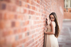 Beautiful sexy girl with long hair and dress perfect shape tanned body possing near wall Stock Photo