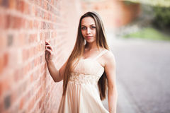Beautiful sexy girl with long hair and dress perfect shape tanned body possing near wall Royalty Free Stock Photography