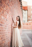 Beautiful sexy girl with long hair and dress perfect shape tanned body possing near wall Royalty Free Stock Photos