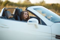 Beautiful girl with long hair in a leather jacket and leather pants in sunglasses sits in an expensive car at stock images