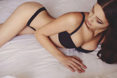 Beautiful sexy girl with long hair in lingerie on the bed Stock Photography
