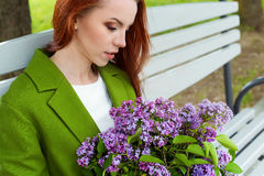 Beautiful sexy girl with long hair in ryzhymi green coat sitting on a park bench with a bouquet of lilac in the hands of Stock Images