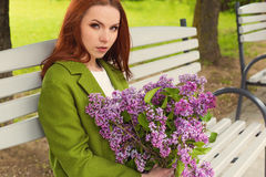 Beautiful sexy girl with long hair in ryzhymi green coat sitting on a park bench with a bouquet of lilac in the hands of Royalty Free Stock Image